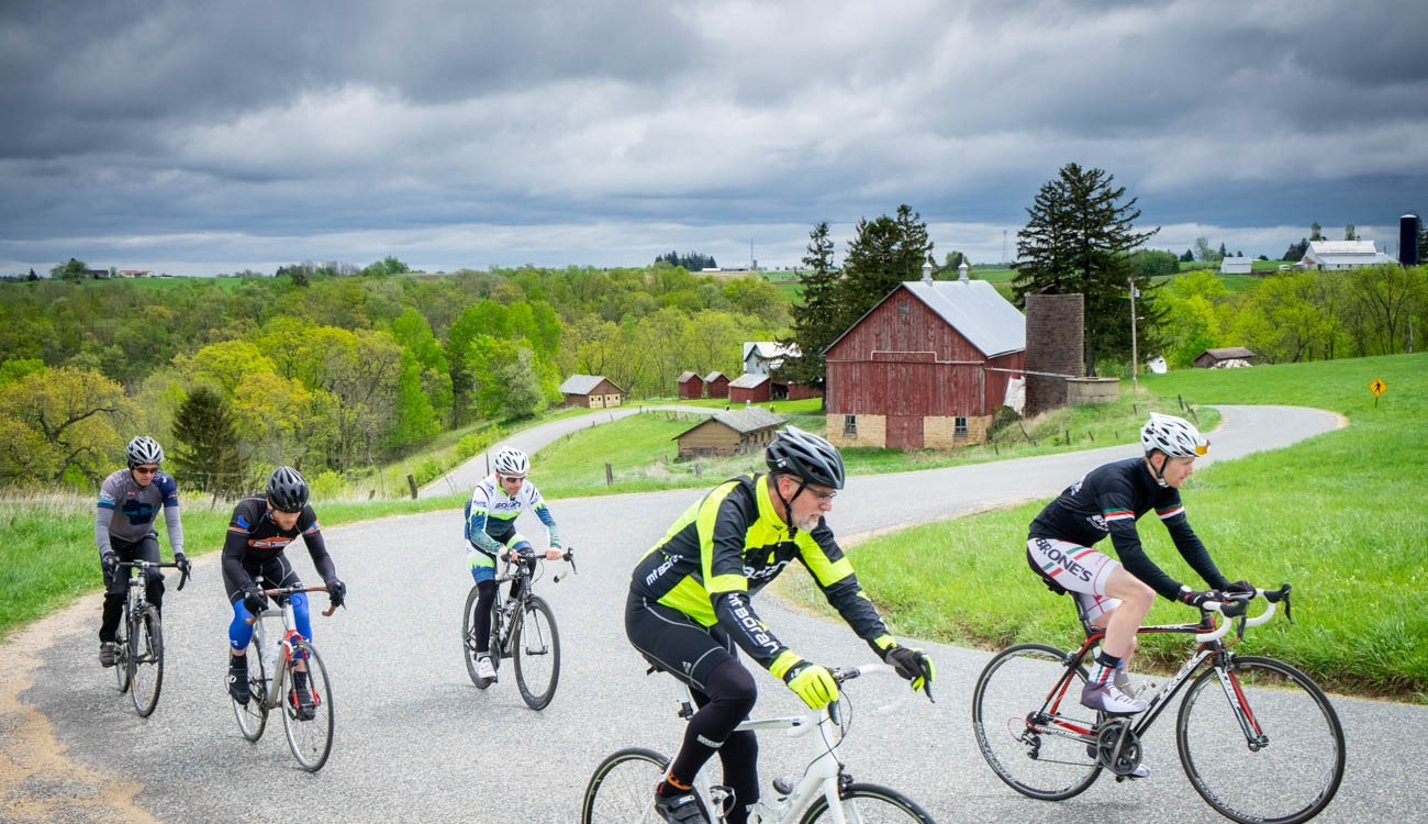 Five riders pedal up a hill on a curvy road with a red barn behind them.
