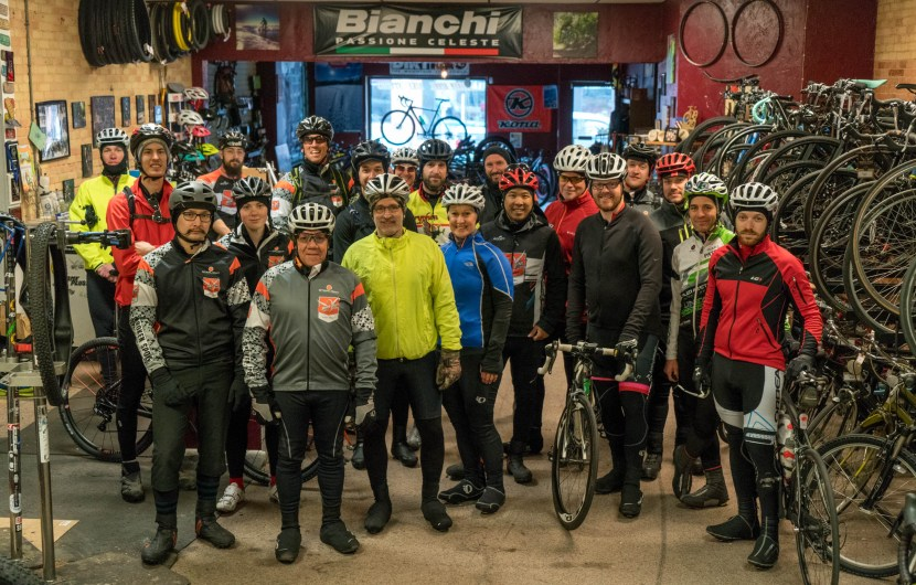 Cyclists stand inside bike shop before ride