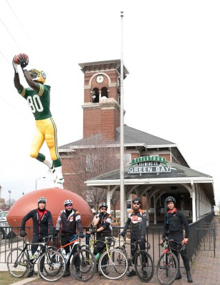 Riders with bikes in front of Title Town Brewery with Green Bay Packer statue over big football