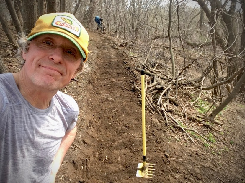 Man in Dekalb hat poses in front of a Mcloed tool on a bench cut trail with a bike in background