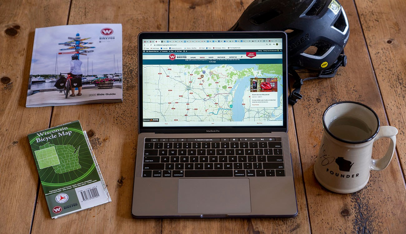 Photo of laptop open to this website with magazine, map, helmet and mug next to it