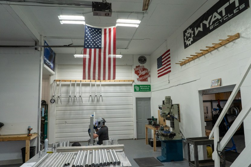 A man welds inside a shop with an american flag and Wyatt Bicycle banner