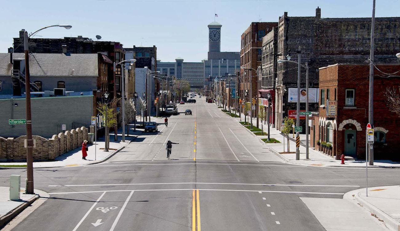 Photo of street with crosswalks, bike lanes, cyclists and woman waiting for bus.