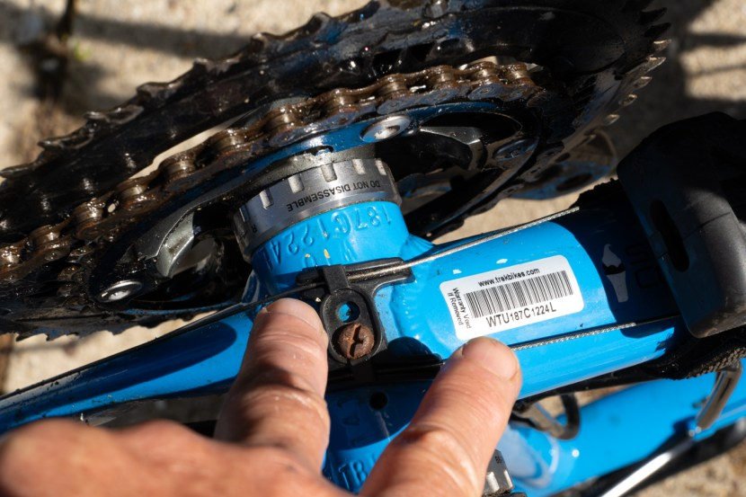 fingers pointing to the serial number stamped on the bottom bracket of a blue bike turned upside down.
