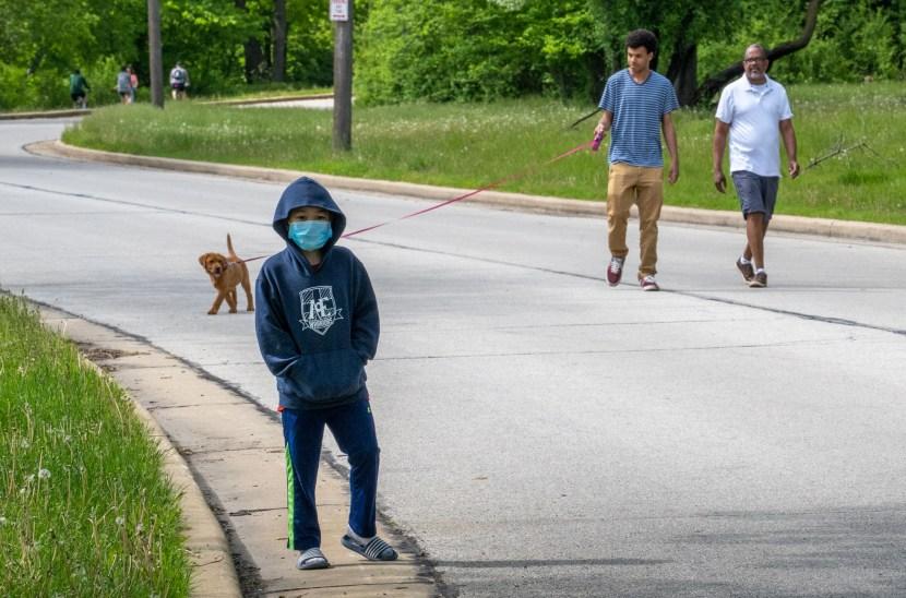 A boy in a hoodie wearing a mask walks in front of two men walking a pupply on a leash