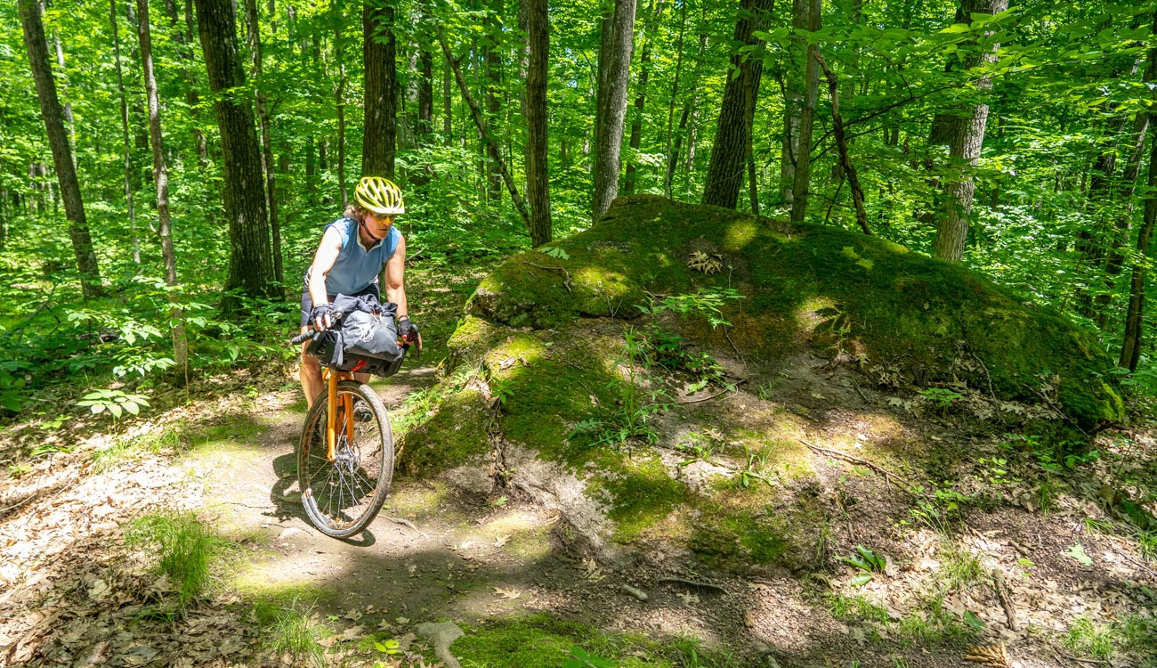 Woman rides past a boulder in the forest