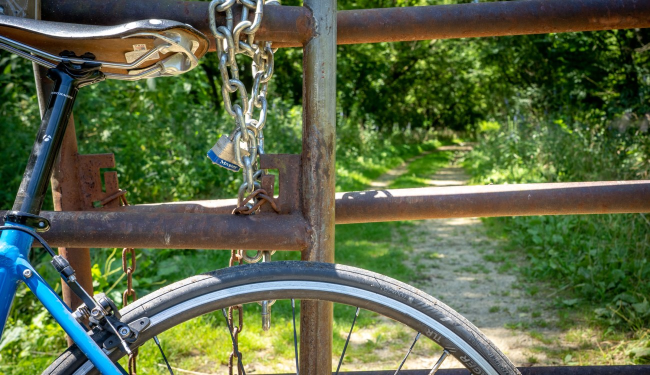bicycle leans against a gate closed with a chain and padlock.