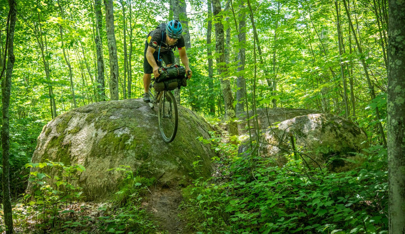 Man rides bike down big boulder in forest