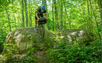 Man rides bike down big boulder in forest