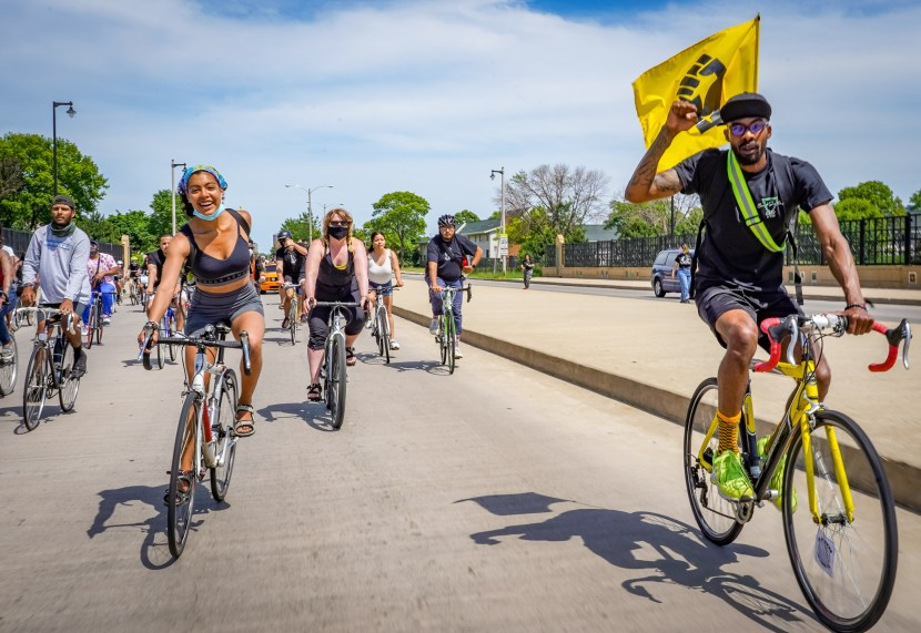 A man on a bicycle with a black power flag rides toward the camera during the black is beautiful ride.