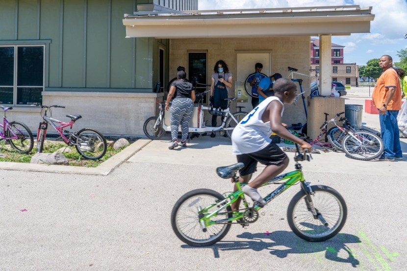 A boy on a bmx bike rides past an active mobile bike repair station.