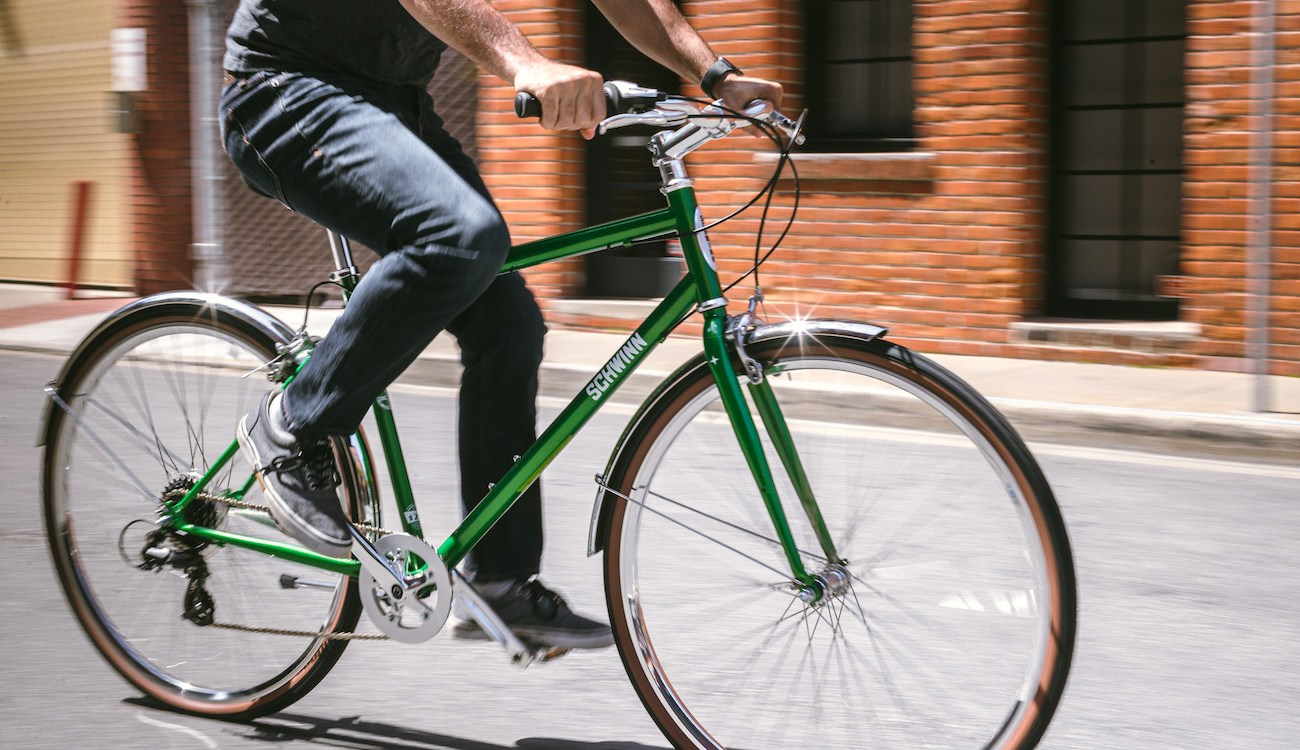 Cropped image of a man riding a green Schwinn Collegiate