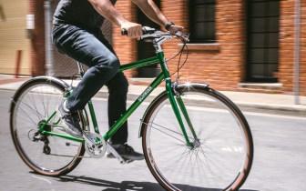 Cropped image of a man riding a green Schwinn Collegiate