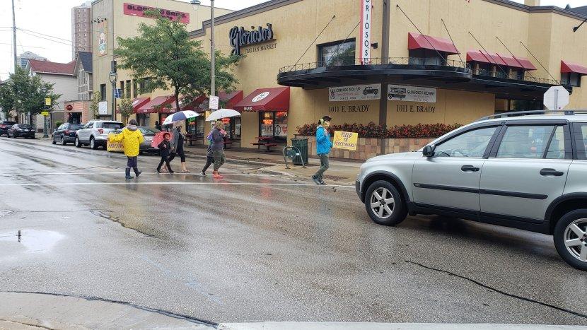 people cross street while car waits