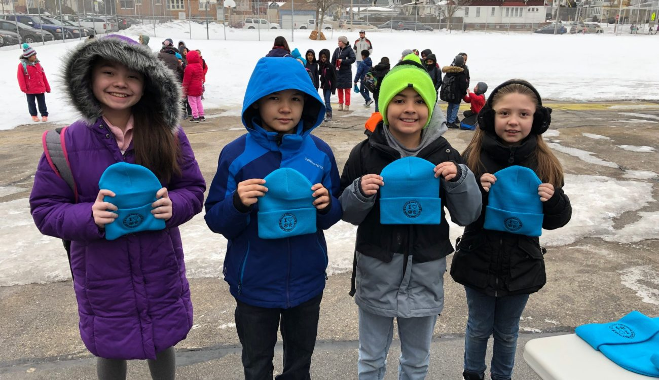 children pose for picture with winter hats