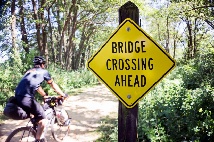 """A """"Bridge Crossing Ahead"""" sign with Art in the background."""