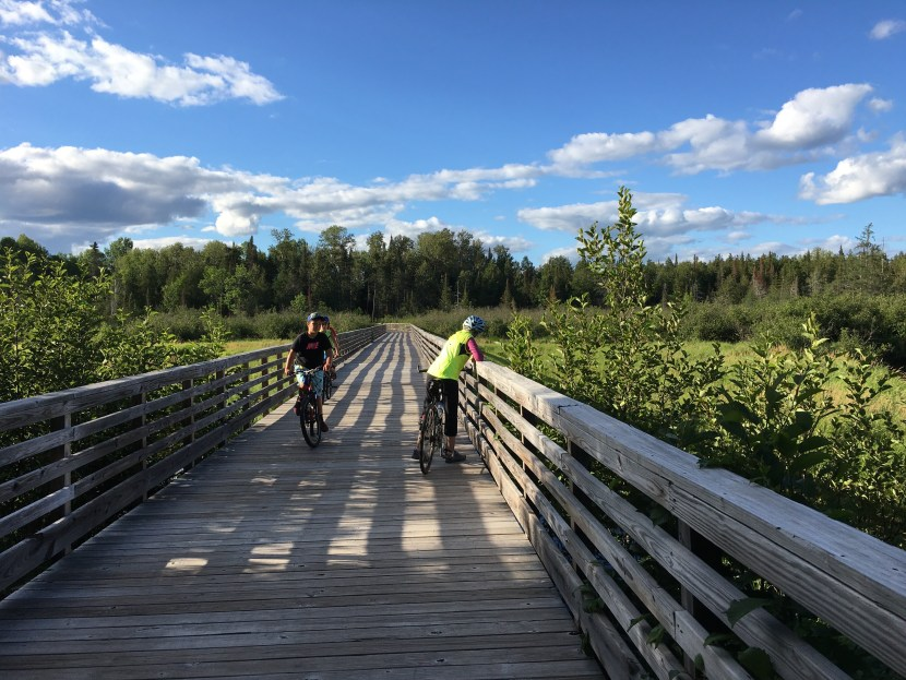 Young riders look over the edge of a boardwalk on the trail.