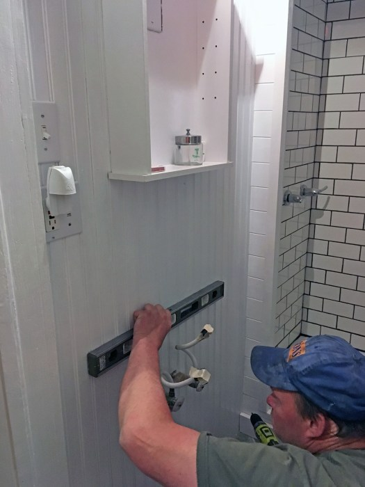 Jim rehanging the sink on the wall
