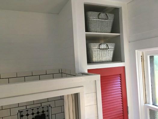 two open shelves above red closet door