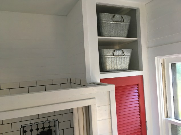 two open shelves above red closet door