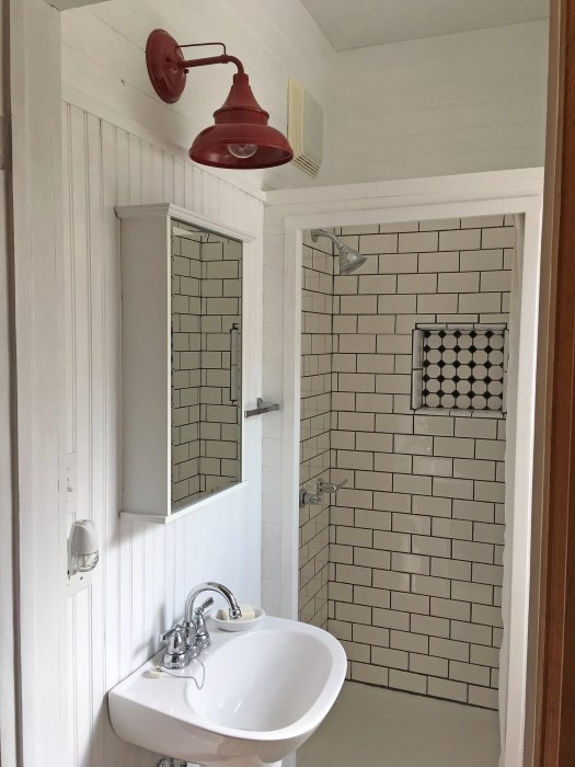 bathroom with white plank walls, red barn light, pedestal sink and subway tile in the shower
