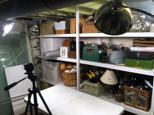 makeshift studio set up in the basement with lights, tripod and table