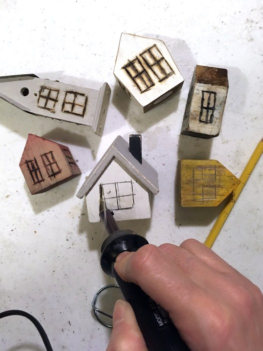 using a woodburner to burn window outlines into little houses