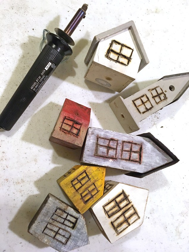 little bird houses being transformed into a mini village