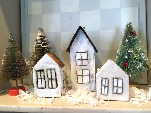 mini Christmas village, made from small birdhouses painted white with woodburned windows