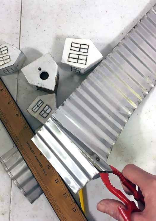 cutting corrugated tin for roofs of mini houses in winter village
