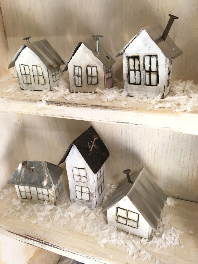 shelves holding little white houses with tin roofs, nail chimneys and faux snow around them