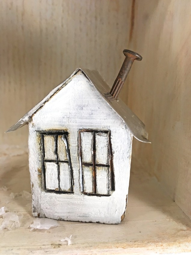distressed little white house with rusty nail chimney