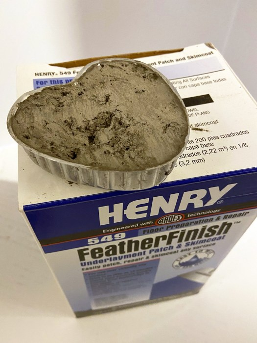 aluminum heart mold filled with cement sitting on top of Henry FeatherFinish Skimcoat