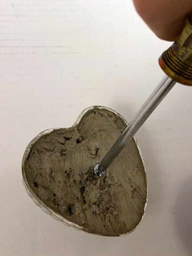 screwing a bolt into heart shaped base filled with concrete