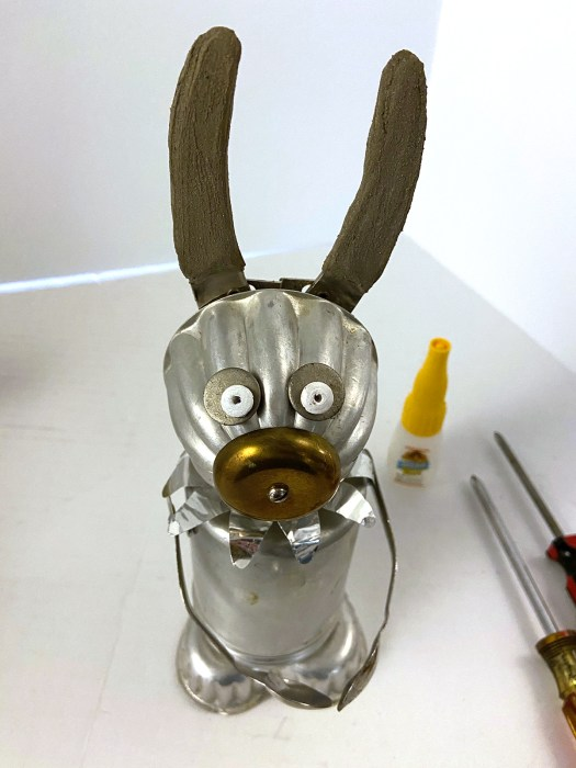 junk rabbit with metal disc eyes and concrete skimcoat ears
