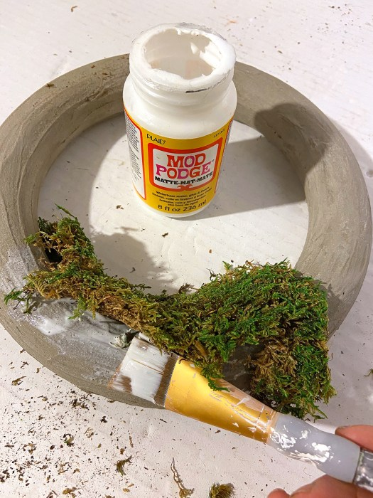 brush painting Mod Podge onto concrete wreath to adhere moss to it