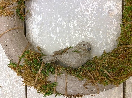 concrete bird nested in moss on the bottom of a wreath