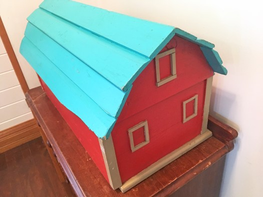 wooden model barn with red walls, an aqua roof and beige window frames