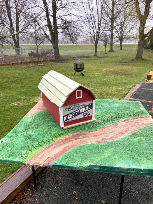 wooden toy barn setting atop a green and brown painted piece of plywood on a table outdoors