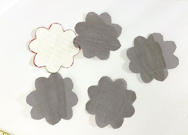 four black mesh window screen pieces cut in the shape of eight-petaled flowers and laying next to the paper template they were cut from