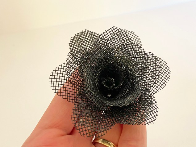 woman's hand holding a larger black mesh flower that will become part of a bouquet of window screen roses