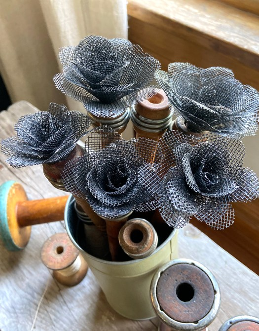 Green metal vase filled with a bouquet of window screen roses on top of vintage wooden spools