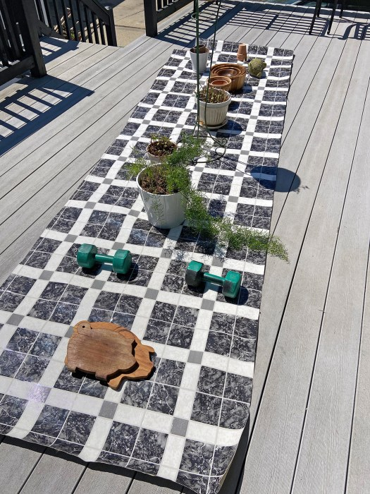 long skinny remnant of black, white and grey vinyl flooring with plants, weights and wood items pressing down the lumps