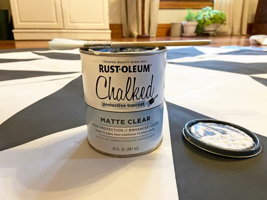 Can of Rust-Oleum Chalked protective topcoat sitting on barn quilt vinyl rug