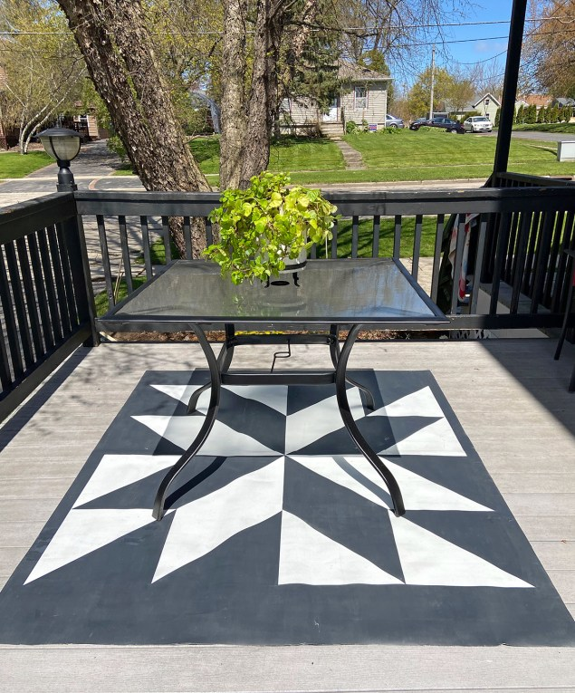 barn quilt patio rug on an outdoor deck with a table sitting on top of it