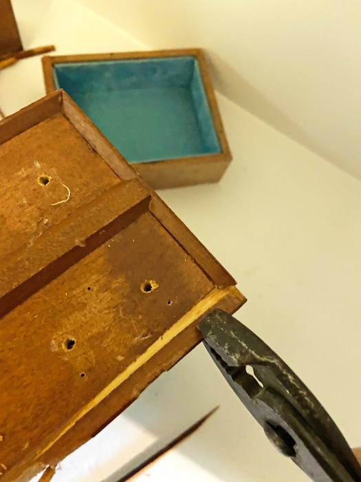 Pliers removing wooden trim on drawer as part of a jewelry box makeover