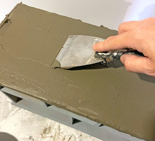 Woman's hand holding a putty knife and applying a cement skimcoat to the top of a jewelry box
