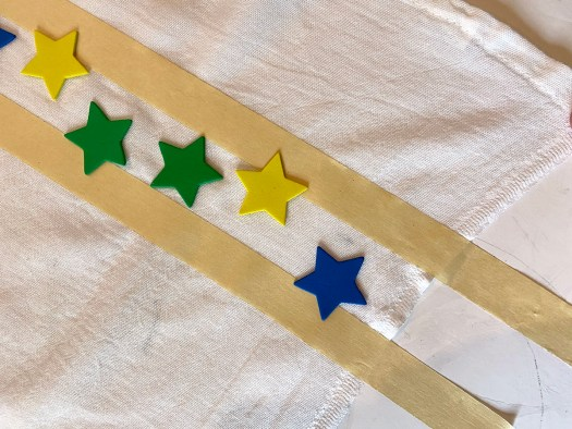 sticking adhesive stars to flour sack dishtowel