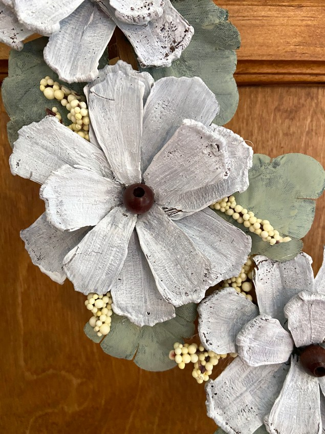 Flowers made from pinecone scales and wooden beads on embroidery hoop wreath