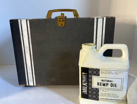 hemp oil bottle in front of vintage black and white thread box